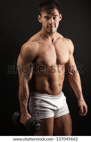 Muscular young man with a dumbbell over black