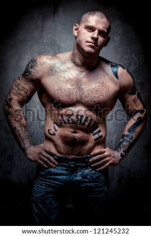 ... young man with many tattoos posing over grey background - stock photo