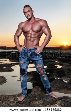 Muscular young naked athletic sexy man in blue jeans posing in the sea at sunset