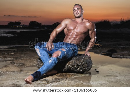 Muscular young sexy naked boy in blue jeans posing on a rock in the sea at sunset