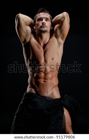 Muscular young sexy naked cute man wrapped in a silk cloth with hands behind head