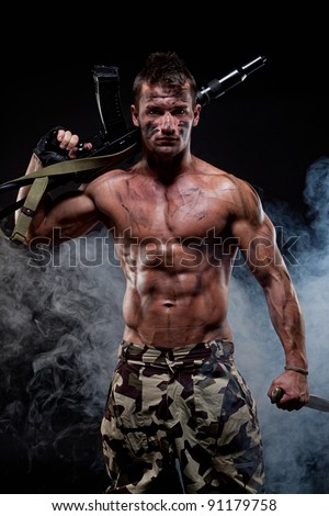 Muscular young sexy naked dirty soldiers with knife and weapons in army clothes and in camouflage paint