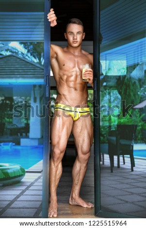 Muscular young sexy naked guy comes out of the house with a glass of juice in swimming trunks