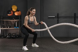 Muscular young smiling woman working out with battle ropes at dark gym, intense functional circuit training. Gray gym background with sports equipment. Crossfit, fitness and workout concept
