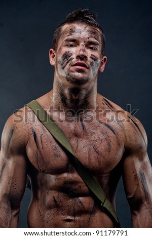 Muscular young wet sexy naked dirty soldiers with weapons behind