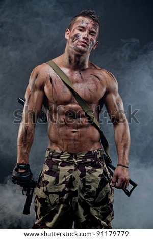 Muscular young wet sexy naked soldiers with weapons in army clothes in the smoke and camouflage paint