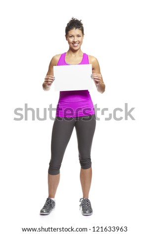 Muscular young woman in sports outfit holding blank card on white background