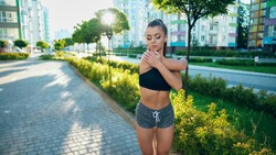 Muscular young woman stretching arms before workout near multistorey buildings in sunny morning. Girl practicing relaxing exercises, warming up upper body outdoors. Sport, flexibility concept.