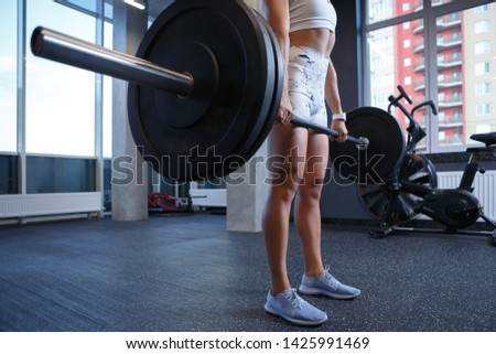 Muscular young woman training with heavy weight barbell in gym club.Strong white girl with pumped muscles holding big barbells doing squat exercises in sportclub.Female strength and healthy lifestyle