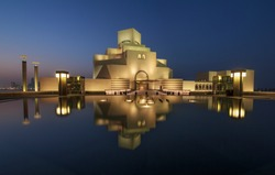 Museum of Islamic Art , Doha,Qatar in daylight exterior view with fountain in foreground and clouds in the sky in the background