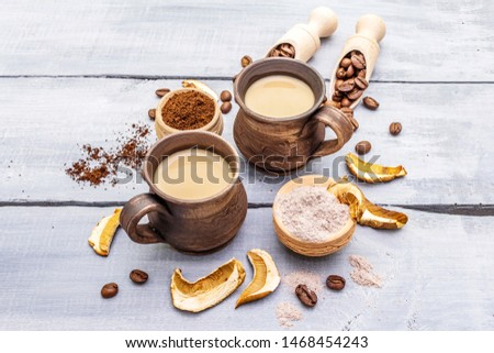 Mushroom Chaga Coffee Superfood Trend. Сeramic bowls and cups, coffee beans, dry mushrooms, powder. Caffeine latte, cappuccino drink, hipster. Wooden boards background, copy space