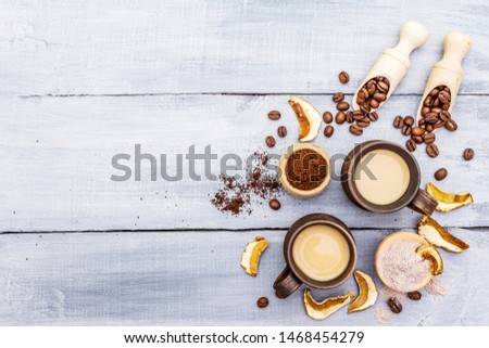 Mushroom Chaga Coffee Superfood Trend. Сeramic bowls and cups, coffee beans, dry mushrooms, powder. Caffeine latte, cappuccino drink, hipster, instagram. Wooden boards background, copy space top view