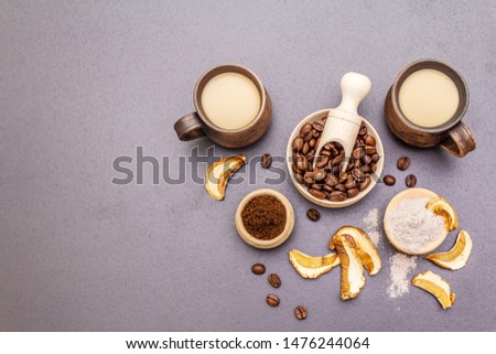 Mushroom Chaga Coffee Superfood Trend. Сeramic bowls and cups, coffee beans, dry mushrooms, powder. Caffeine latte, cappuccino drink, hipster, instagram. Stone concrete background, top view copy space