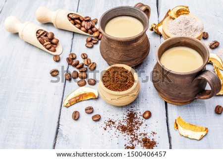 Mushroom Chaga Coffee Superfood Trend. Сeramic bowls and cups, coffee beans, dry mushrooms, powder. Caffeine latte, cappuccino drink, hipster. Wooden boards background, copy space close up