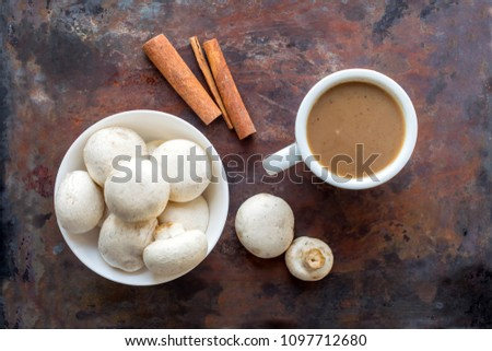 Mushroom Coffee Superfood Trend. Cup of coffee and white bowl with mushrooms on wooden background with sunlight. Caffeine latte, drink, hipster, instagram trend. Coffees for best energy and creativity