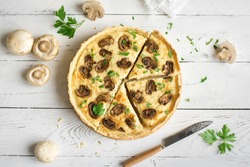 Mushroom Quiche Pie  with champignons and cheese on white wooden background, top view. Savory tart with mushrooms.