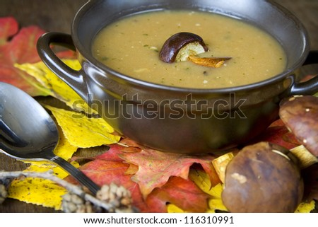 Mushroom soup and autumnal leaves on a brown table