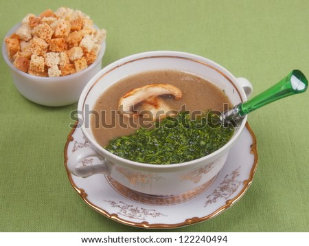 Mushroom soup with croutons on a green background