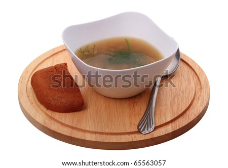 Mushroom soup with rye bread. In a white bowl on a cutting board