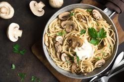 Mushroom Spaghetti Pasta and cream sauce on rustic background, top view. Homemade italian pasta with champignon mushroom in cooking pan.