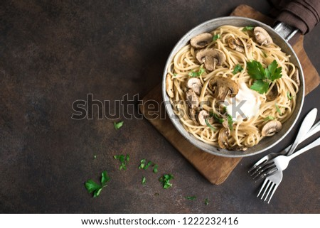 Mushroom Spaghetti Pasta and cream sauce on rustic background, top view. Homemade italian pasta with champignon mushroom in cooking pan.