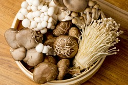 Mushrooms. Fresh Organic, enoki, shiitaki, hen of the woods, baby portabello, button mushrooms in wooden woven basket at a restaurant. Variety of Mushrooms in a basket, closeup and shot overhead.