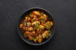 Mushrooms Manchurian dry in black bowl at dark slate background. Mushroom Manchurian - is indo chinese cuisine dish with deep fried mushrooms, bell peppers, sauce and onion.