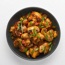 Mushrooms Manchurian dry in black bowl isolated at white background. Mushroom Manchurian - is indo chinese cuisine dish with deep fried mushrooms, bell peppers, sauce and onion.