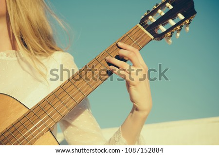 Music and entertainment concept. Guitar with fingers strumming strings. Hand play on string instrument. Classic guitar neck fretboard and headstock on sunny blue sky. - Shutterstock ID 1087152884