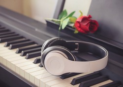 Music and entertainment concept.Music headphone on piano keyboard with red rose.vintage filtered,selective focus.