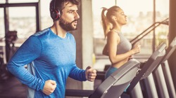 Music and exercises go together. Couple working exercise on treadmill. Focus is on man.