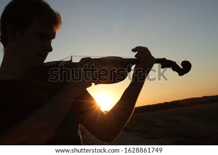 Music arrange of silhouette of man playing the violin at sunset, sunrise. Player, instrument and skyline is black and light sun and blue sky is on background. Copy space (empty, free place) for text. Сток-фото ©