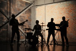 Music band and fashion. Handsome young men in suits playing rock and singing song. Bands silhouettes with on a concert.