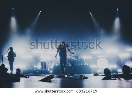 Music band / group silhouette perform on a concert stage.  Dark background, smoke, concert  spotlights, singer holds a microphone stand. #683216719