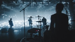 Music band group silhouette perform on a concert stage.   silhouette of drummer playing on drums audience holding cigarette lighters and mobile phones