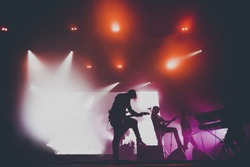 Music band / group with guitar player / guitarist silhouette perform on a concert stage.  Dark background, smoke, concert  spotlights