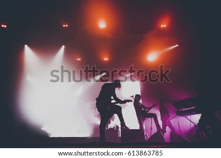 Music band / group with guitar player / guitarist silhouette perform on a concert stage.  Dark background, smoke, concert  spotlights #613863785