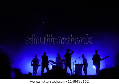 music band playing on concert stage, silhouettes of musicians unrecognizable, group of people singing together in rock festival #1148435162