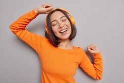 Music beat for energetic mood. Upbeat Asian woman enjoys favorite song perfect sound in headphones moves actively dressed casually. This melody drives her dance. Cheerful female dj full of energy