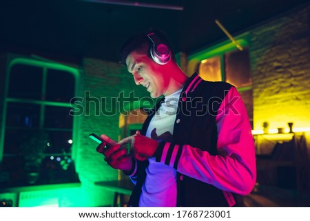 Music. Cinematic portrait of stylish man in neon lighted interior. Toned like cinema effects, bright neoned colors. Caucasian model using gadgets, devices in colorful lights indoors. Youth culture. Foto stock ©