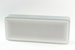 Music column, Wireless music column. White with with gray metal case bluetooth speaker. On a white background.