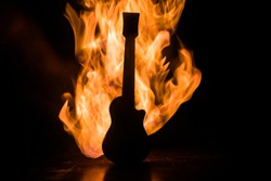 Music concept. Acoustic guitar on a dark background under beam of light with smoke with copy space. Exploding guitar. Fire effects. Surreal guitar. Selective focus