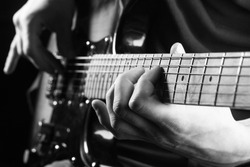 Music concept. Guitar acoustic. Play the guitar. Live music. Music festival. Instrument on stage, band. Electric guitar, guitarist, musician rock. Musical instrument. Guitars, strings. Black and white