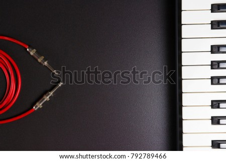 Photo of Music concept. Making music. Piano keys and guitar cable on black background with free space