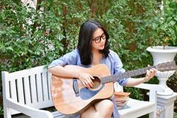 Music Concepts. Asian girls playing guitar. Asian women relaxing with music. Asian women have a happy lifestyle. Beautiful Asian girl playing guitar in the garden.