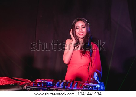 Music Concepts. DJ is rhythm music with Controller and mixer. DJ is playing the song at the party. Young are adjusting the music with the controller. The fun of music and light colors. #1041441934