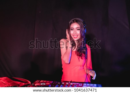 Music Concepts. DJ is rhythm music with Controller and mixer. DJ is playing the song at the party. Young are adjusting the music with the controller. The fun of music and light colors. #1041637471