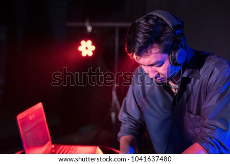 Music Concepts. DJ is rhythm music with Controller and mixer. DJ is playing the song at the party. Young are adjusting the music with the controller. The fun of music and light colors. #1041637480
