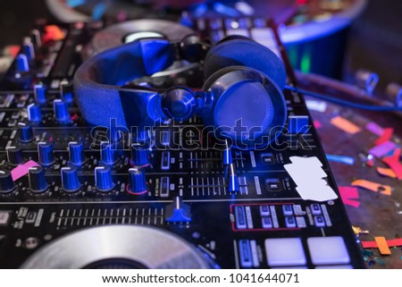 Music Concepts. DJ is rhythm music with Controller and mixer. DJ is playing the song at the party. Young are adjusting the music with the controller. The fun of music and light colors. #1041644071