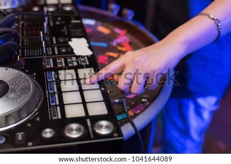 Music Concepts. DJ is rhythm music with Controller and mixer. DJ is playing the song at the party. Young are adjusting the music with the controller. The fun of music and light colors. #1041644089